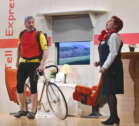 Sichtlich verärgert über die Zerlegung seines Fahrrads beschwert sich der Besitzer (Philipp Wenk) bei der enervierten Kellnerin Trudi (Hildegard Rüttimann) über die Zustände im Tell-Express.