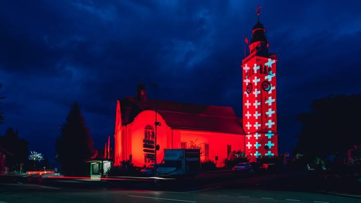 Der Kirchturm von Aeschi in ungewohntem Licht: ganz in rot mit weissen Kreuzen.