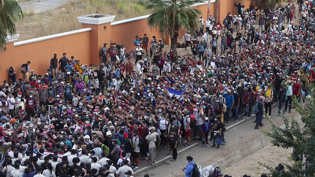 Migranten aus Honduras stehen vor Polizisten, die eine Strasse blockieren.