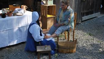 Mittelalter am «Mülifescht»: Kräuterfrau massiert mit Ölen die Füsse einer Besucherin. (rgy)
