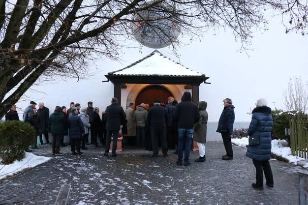Eingemummt warten Besucher am frühen Abend darauf, dass die Kirchentür geöffnet wird.