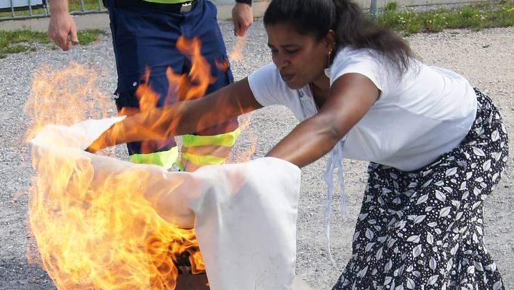 Mit einer Löschdecke werden die Flammen erstickt.