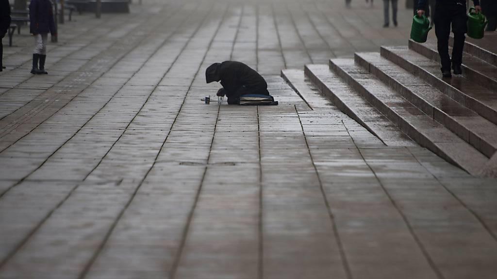 ARCHIV - Eine Bettlerin kniet auf der Königstraße in Stuttgart. Foto: picture alliance / dpa