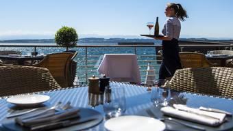 Preisdruck unter freiem Himmel? Eine Frau serviert Wein auf der Terrasse eines beim Neuenburgersees gelegenen Hotels