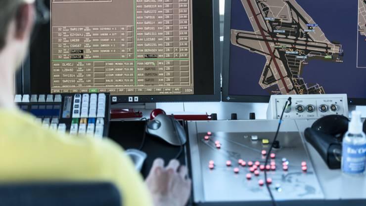 Ein Mitarbeiter von Skyguide kontrolliert die Monitore, hier im Tower des Flughafen Zürich Kloten. (Archivbild)