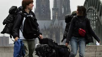 Diese jungen Leute dürften ab 1. März mit ihrem grossen Gepäck nicht mehr in den hinter ihnen aufragenden Kölner Dom (Archiv)