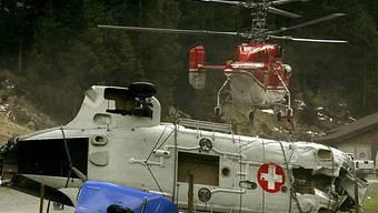 Im Vordergrund das Wrack, im Hintergrund der Bergungshelikopter