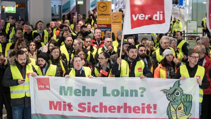 Mitglieder der Gewerkschaft Verdi stehen am Flughafen Köln mit Fahnen und einem Transparent.