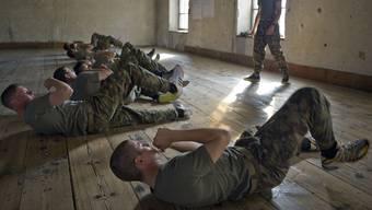 Rekruten machen Rumpfbeugen auf dem Dachboden im Zeughaus südlich der Rohrerstrasse.