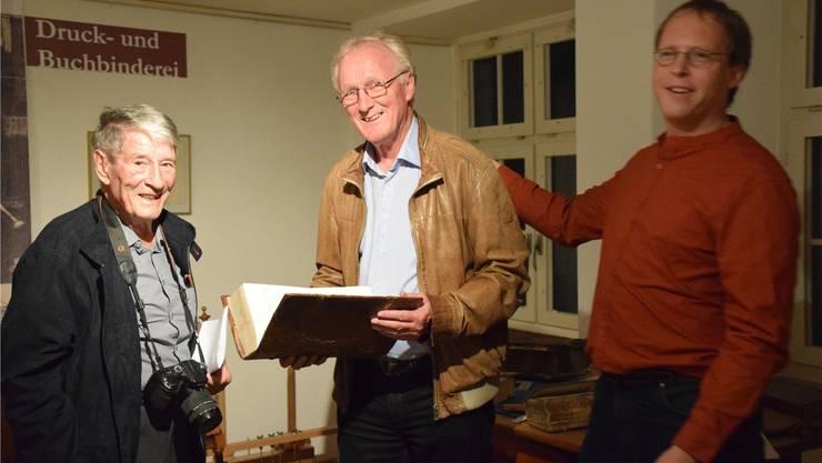 Museumsleiter Hannes Burger (Mitte) freut sich mit Stifter Robert Meyer (links) und Norbert Plumhof über die restaurierte Bibel. Bild: dd