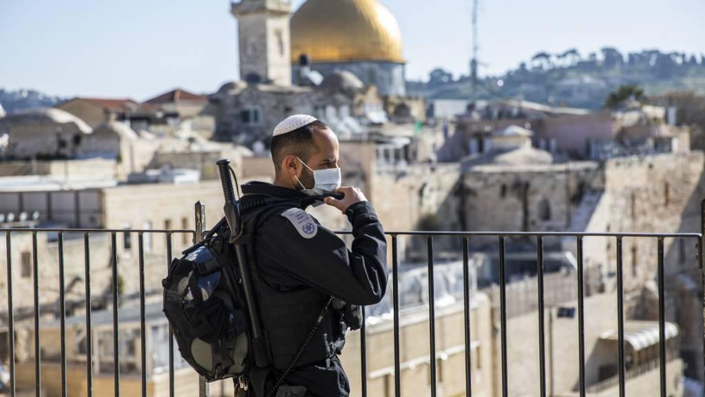 ARCHIV - Ein israelischer Polizist mit Mundschutz steht in der Altstadt von Jerusalem Wache. Im Hintergrund der Felsendom auf dem Tempelberg. Foto: Ilia Yefimovich/dpa