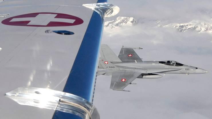 Eine F/A-18 fliegt während einer Übung fürs WEF neben einem zivilen Flugzeug.