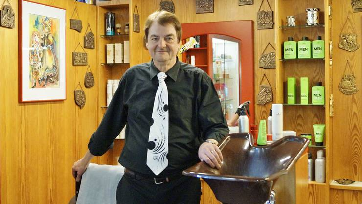 Ein Coiffeursalon der besonderen Art: Bruno von Niederhäusern mit passender Krawatte vor seiner «Fasnachtsecke» mit den vielen Plaketten.