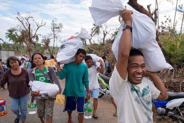 Taifun-Opfer tragen Hilfsgüter mit sich. Transportschiffe sind in Tacloban, der am schwersten getroffenen Region angekommen.