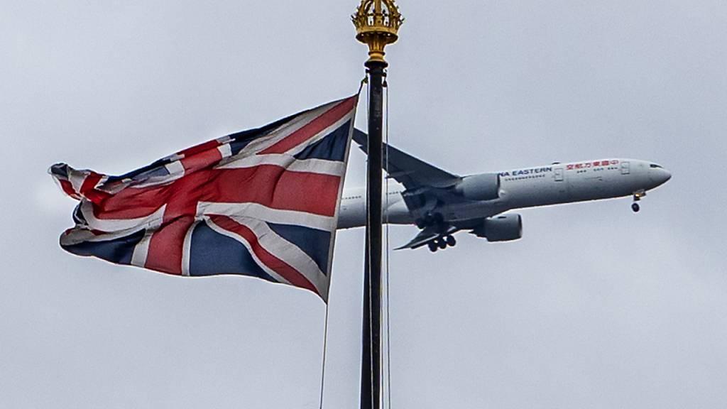 ARCHIV - Ein Flugzeug überfliegt den Palast of Westminster mit der gehissten brittischen Fahne. Foto: Richie Hancox/RMV via ZUMA Press/dpa