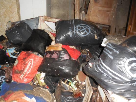 Im Kellerraum stapeln sich Abfallsäcke.