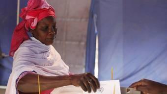 Eine Frau gibt im Senegal ihre Stimme ab