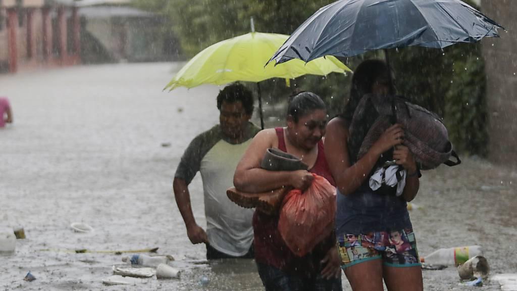 Menschen bringen sich in Sicherheit. Aufgrund des Tropensturms «Eta» wurden in Honduras Überschwemmungen und Erdrutsche gemeldet. Etwa 30 Ortschaften wurden von der Außenwelt abgeschnitten, weil Brücken einstürzten. Foto: Delmer Martinez/AP/dpa