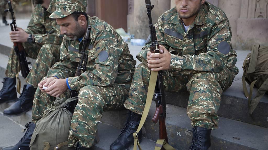 Armenische Freiwilligenrekruten versammeln sich an einem Ort, an dem sie ihre Uniformen und Waffen erhalten, bevor sie an die Frontlinie entsandt werden. Die verfeindeten Südkaukasusrepubliken Armenien und Aserbaidschan liefern sich schwere Kämpfe um die Konfliktregion Berg-Karabach. Foto: Karen Mirzoyan/AP/dpa
