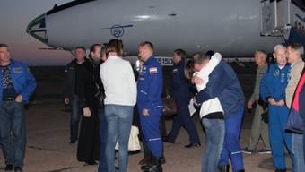 Wohlauf: US-Astronaut Nick Hague wird bei seiner Ankunft am Flughafen von Baikonur umarmt. In der Bildmitte sein russischer Kollege Alexej Owtschinin.