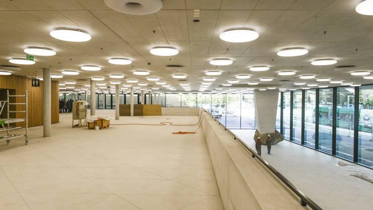 Ein Blick ins neue Foyer: Weisse Böden, Gastro-Stände aus Holz, Donut-Lampen und ein Findling, auf dem das Dach ruht.