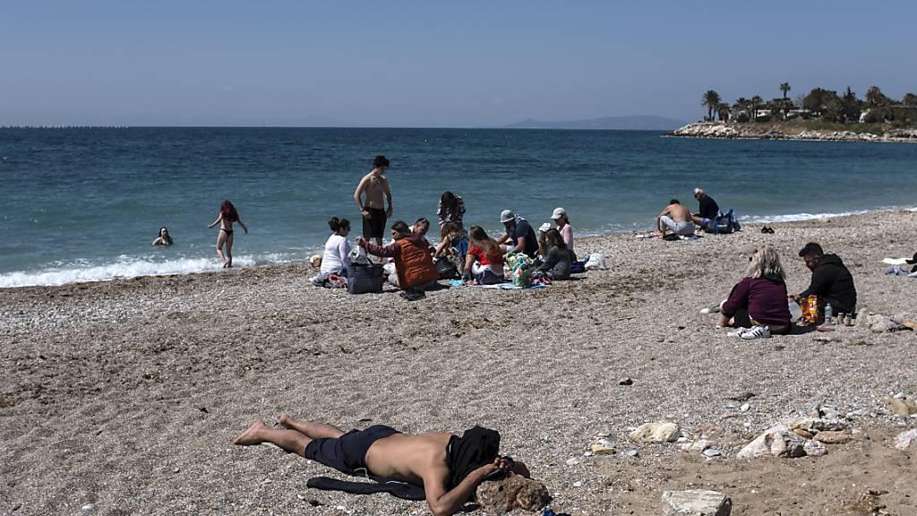 Menschen genießen einen sonnigen Tag an einem Strand im Athener Vorort Glyfada. Foto: Yorgos Karahalis/AP/dpa