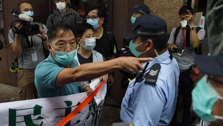 Die Polizei stoppt am Freitag Pro-Demokratie-Aktivisten auf den Strassen von Hongkong. (Bild: Keystone)