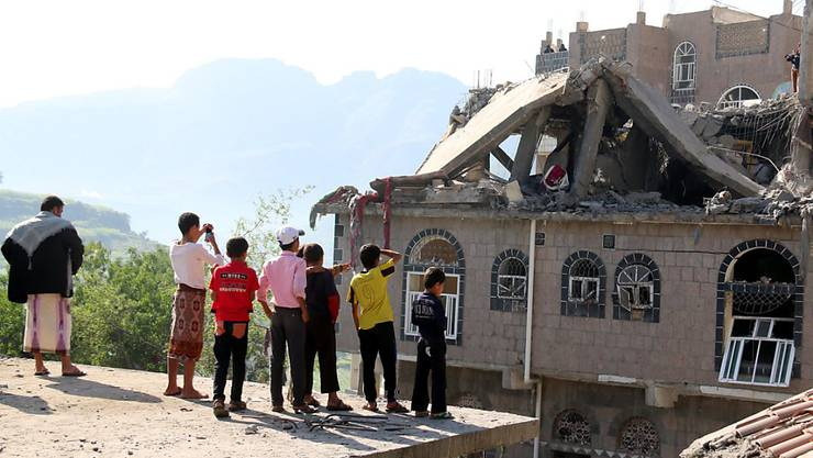 Kinder in der jemenitischen Stadt Ibb betrachten ein zerbombtes Haus - der Bürgerkrieg im Land trifft hunderte Unbeteiligte.