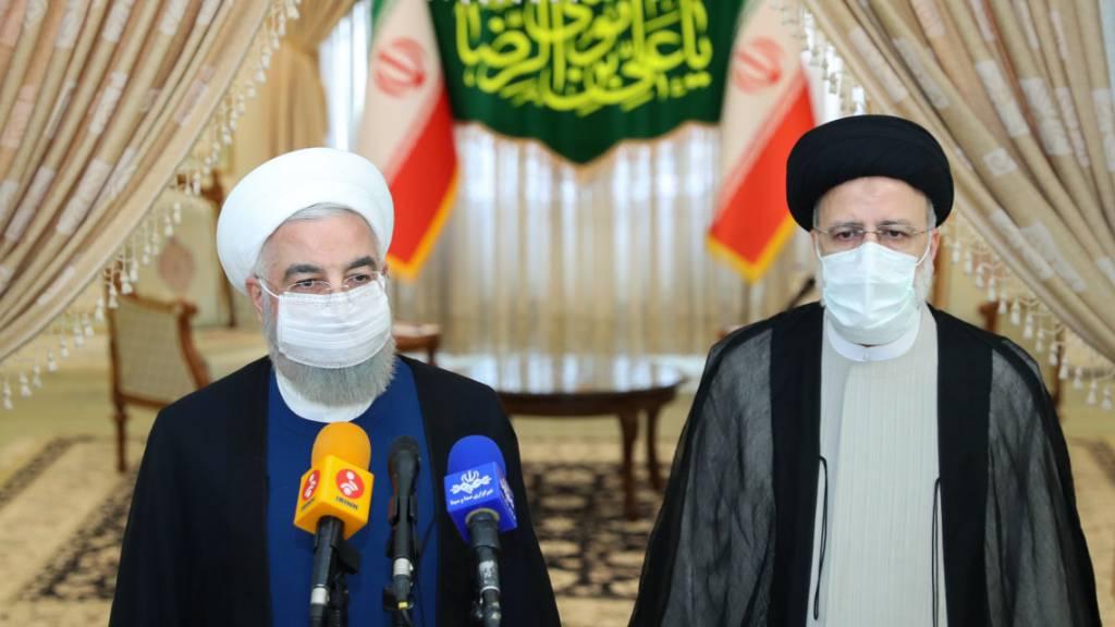 HANDOUT - Der scheidende iranische Präsident Hassan Rouhani (l) spricht neben dem gewählten iranischen Präsidenten Ebrahim Raisi bei einer Pressekonferenz. Foto: -/Iranian Presidency/dpa - ATTENTION: editorial use only and only if the credit mentioned above is referenced in full