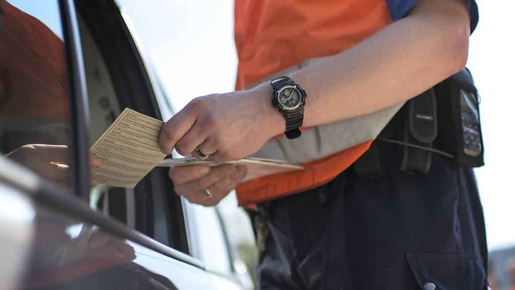 Beamte der Polizei Basel-Landschaft begutachten bei einer Kontrolle Fahrzeugpapiere und den Führerausweis. (Archivbild)