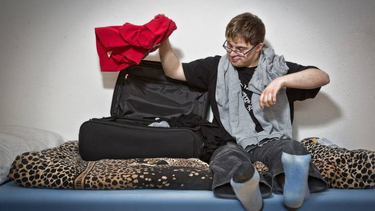 Matthias Brücker hat es sich auf dem Bett bequem gemacht und zeigt, wie er jeweils seinen Koffer packt: Mit viel Schwung