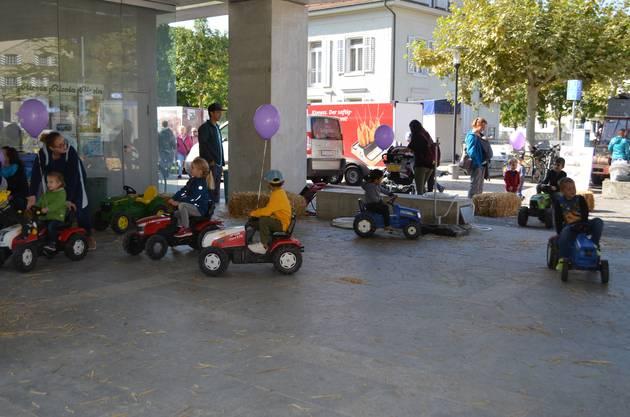 Kinder fahren mit Traktoren umher.