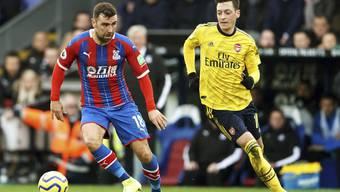 James McArthur von Crystal Palace behauptet den Ball gegen Mesut Özil