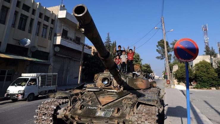 Kinder machen das Vicotry-Zeichen auf einem Panzer in Aleppo