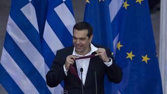 Zum Abschluss seiner Rede bindet Tsipras die Krawatte wieder los.