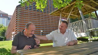 Heimleiter Uwe Tischer zusammen mit Manfred, einem in Muri bekannten Bewohner des Roth-Hauses; im Hintergrund die Beschäftigungsstätte.
