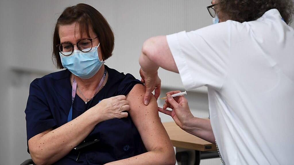 Eine Krankenpflegerin erhält in der Universitätsklinik Helsinki den Corona-Impfstoff von Biontech/Pfizer. Foto: Antti Aimo-Koivisto/Lehtikuva/dpa