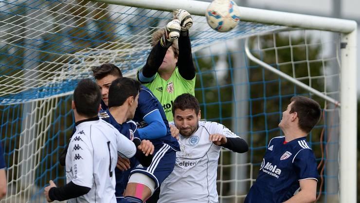 Wackers Goalie Nico Allemann faustet den Ball vor Andreas Siragusa von Italgrenchen weg.