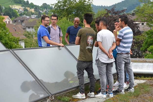 Auf dem Dach des Regionalen Pflegezentrums Baden erklärt Marc Hutter, stellvertretender Leiter Unterhaltsdienst, den Asylsuchenden seinen Arbeitsbereich.