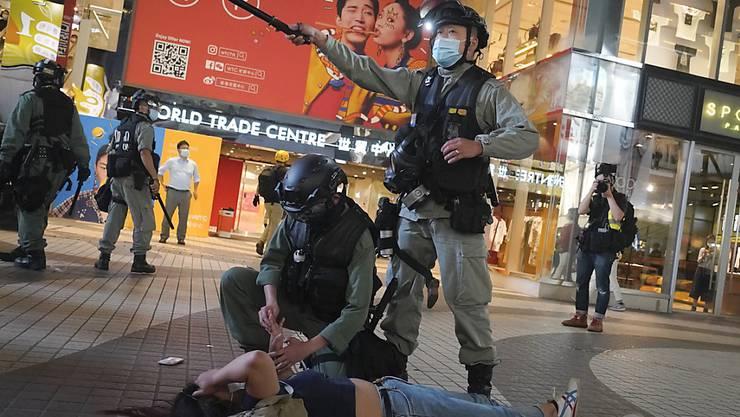 dpatopbilder - Bereitschaftspolizisten verhaftet eine Demonstrantin während einer Demonstration im Einkaufsviertel Causeway Bay. Foto: Vincent Yu/AP/dpa