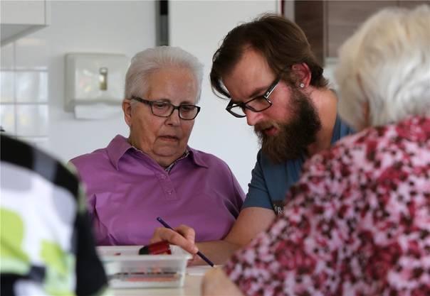 Pflegefachmann Jörg Seidl hilft einer demenzkranken Frau beim Zeichnen ihres Bildes.