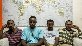 Vier Asylbewerber vor einer Weltkarte