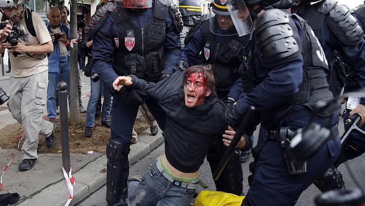 In Paris wird ein verwundeter Demonstrant von der Strasse weggebracht.
