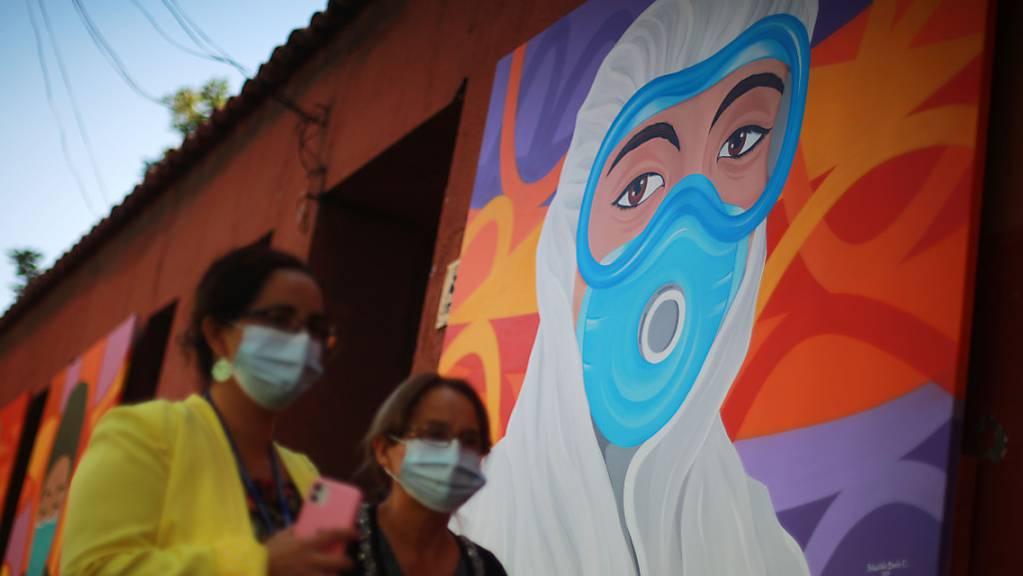 Zwei Frauen mit Masken gehen an einem Wandgemälde zur Anerkennung der Mitarbeiter des Gesundheitswesens bei der Bekämpfung des Covid-19 vorbei. (Archivbild)
