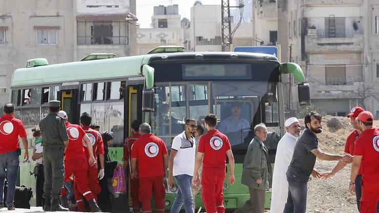 Mitarbeiter des syrischen Halbmondes und der Regierung bringen gemäss einer Vereinbarung Aufständische mit Angehörigen vom belagerten Homs-Stadtteil Al-Waer in nördliche Rebellengebiete