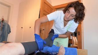 Die Spitex-Fachangestellte Claudia Hofmann zieht einem Kunden Stützstrümpfe über. eva