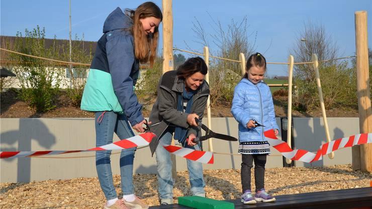 Vania Singer (6.Klasse), Diana Wittwer (Schulpflegepräsidentin) und Soraya Rüttimann (Kindergarten) eröffnen feierlich den neuen Spielplatz. Christian Breitschmid