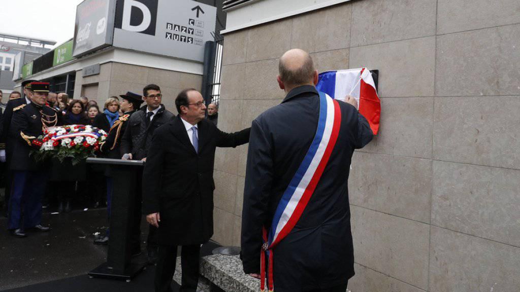 Frankreichs Präsident François Hollande (l.) und der Bürgermeister von Saint-Denis, Didier Paillard, enthüllen am Stade de France nördlich der Hauptstadt Paris eine Gedenkplakette.