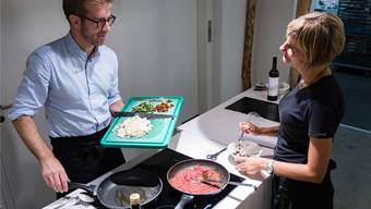 Kursleiterin Anne Treccarichi erklärt Regierungskandidat Conradin Cramer das vegane Kochen.