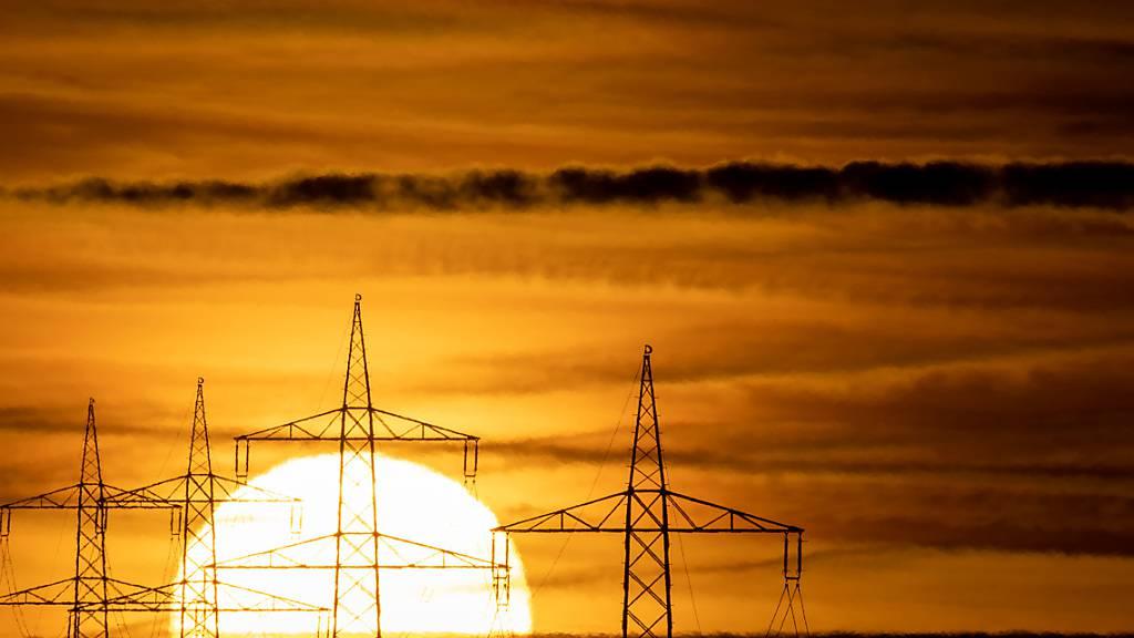 ARCHIV - Die Sonne geht hinter Hochspannungsmasten auf. Foto: Sebastian Gollnow/dpa